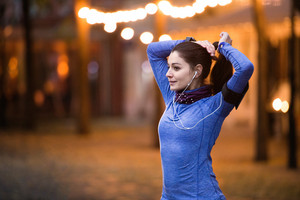 Beautiful young runner with armband and earphones, listening music, warming up and stretching in the illuminated night town.