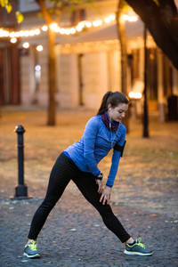 Beautiful young runner with armband and earphones, listening music, warming up and stretching legs in the illuminated night town.