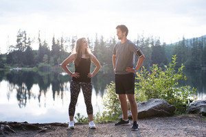 Beautiful young runners at the lake in green nature, resting, arms on hips.