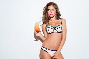 Beautiful young sexy girl holding cocktail wearing bikini isolated on the white background