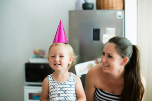 Beautiful young smiling mother and her cute little daughter wearing pink party hat on head prepared to celebrate birthday.