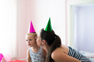 Beautiful young smiling mother giving a kiss to her cute little daughter wearing colorful party hats on heads prepared to celebrate birthday.