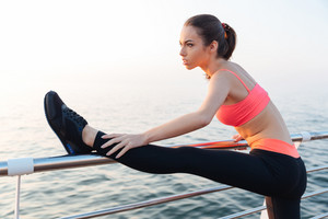 Beautiful young sportswoman stretching legs on pier near the sea