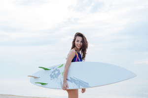 Beautiful young surfer girl in swimming suit holding white surfboard at the beach