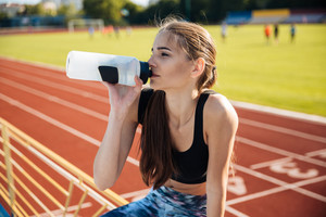 Beautiful young tired fitness girl drinking water after workout at the stadium