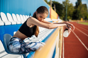 Beautiful young tired fitness girl resting after workout at the stadium