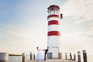 Beautiful young wedding couple in front of lighthouse