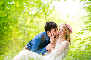 Beautiful young wedding couple kissing outside in green forest. Bride in white dress and floral wreath and groom in denim shirt.