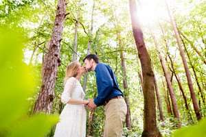 Beautiful young wedding couple kissing outside in green forest. Bride in white dress and groom in denim shirt.