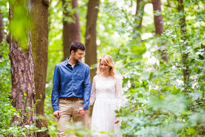 Beautiful young wedding couple on a walk outside in green forest, holding hands. Bride in white dress and groom in denim shirt.