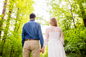 Beautiful young wedding couple outside in green forest. Bride in white dress and groom in denim shirt. Rear view.