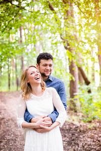 Beautiful young wedding couple outside in green forest. Bride in white dress and groom in denim shirt.