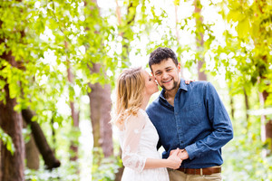 Beautiful young wedding couple outside in green forest. Bride in white dress kissing her groom in denim shirt.