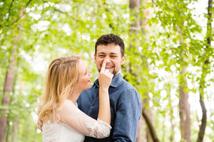 Beautiful young wedding couple outside in green forest. Bride in white dress touching nose of her groom wearing denim shirt.