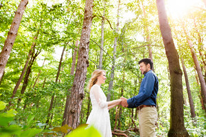Beautiful young wedding couple outside in green forest, holding hands. Bride in white dress and groom in denim shirt.