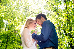 Beautiful young wedding couple outside in green forest, touching foreheads. Bride in white dress and groom in denim shirt.