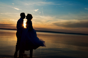 Beautiful young wedding couple standing on the beach