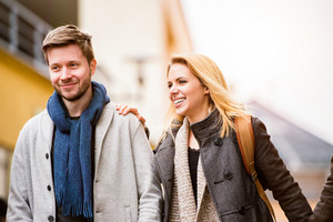 Beautiful young woman and man on a walk in town, talking and laughing