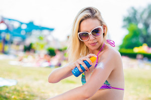 Beautiful young woman applying sunscreen on her shoulders