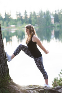 Beautiful young woman at the lake in green nature, stretching and warming up.