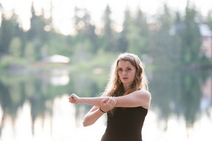 Beautiful young woman at the lake in green nature, stretching arms and warming up.