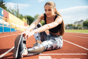 Beautiful young woman athlete sitting and stretching legs on stadium