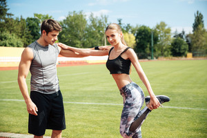 Beautiful young woman athlete standing and stretching with personal trainer on stadium