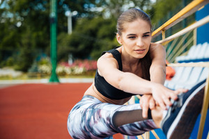 Beautiful young woman athlete stretching legs and working out on stadium