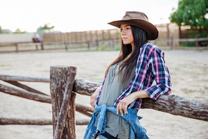 Beautiful young woman cowgirl in hat and plaid shirt standing and relaxing outdoors