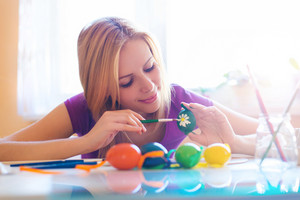 Beautiful young woman hand painting easter eggs