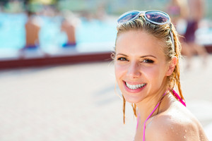 Beautiful young woman having fun outside at the swimming pool
