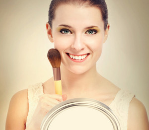 Beautiful young woman holding a makeup brush