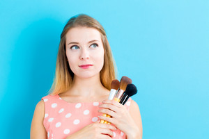 Beautiful young woman holding makeup brushes on a blue background