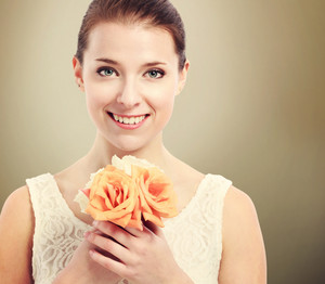 Beautiful young woman in a white dress holding roses