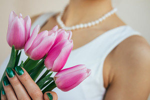 Beautiful young woman in a white dress with a necklace holding a pink tulips