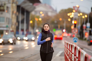 Beautiful young woman in black vest running in the city against road with cars