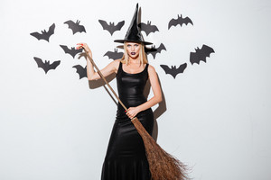 Beautiful young woman in black witch costume with hat and broom standing over white background