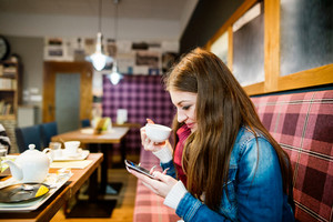 Beautiful young woman in cafe, drinking tea, holding a smart phone, texting