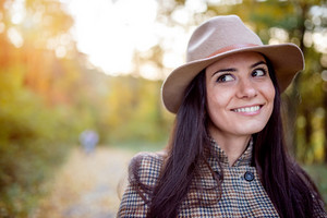 Beautiful young woman in checked coat and brown hat in autumn forest