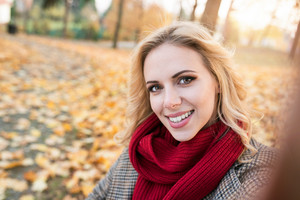 Beautiful young woman in checked coat and red knitted scarf in autumn park taking selfie