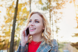 Beautiful young woman in checked coat and red sweater with smart phone in autumn park