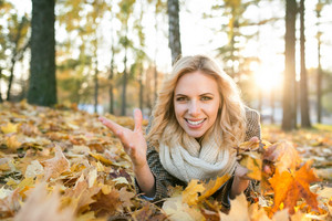 Beautiful young woman in checked coat and white knitted scarf in autumn park lying on the ground, throwing yellow tree leaves in the air