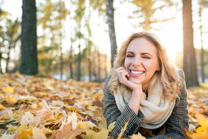 Beautiful young woman in checked coat and white knitted scarf in autumn park lying on the ground