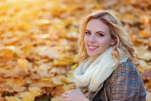 Beautiful young woman in checked coat and white knitted scarf in autumn park sitting on the ground covered with yellow leaves