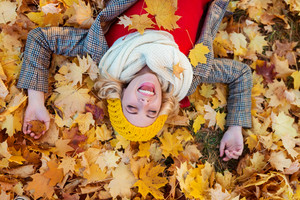 Beautiful young woman in checked coat, white knitted scarf and yellow hat in autumn park lying on the ground against yellow leaves