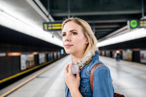 Beautiful young woman in denim shirt with earphones, standing at the underground platform, waiting
