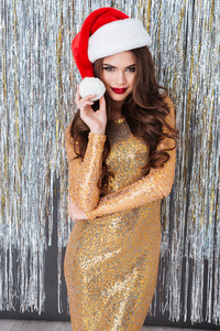 Beautiful young woman in golden dress and santa claus hat standing over sparkling background