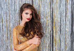 Beautiful young woman in golden dress standing over shining background