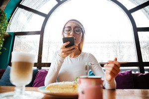 Beautiful young woman in hat and glasses taking of her food with mobile phone in cafe