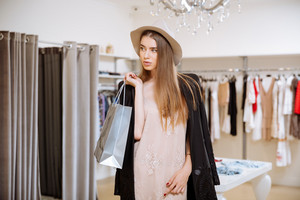 Beautiful young woman in hat standing and holding shopping bags in fashion boutique
